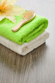 Flower on towels with hairbrush — Stock Photo