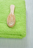 Wooden hairbrush on green towel — Stok fotoğraf