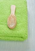 Yeşil havlu üzerinde ahşap saç fırçası — Stok fotoğraf