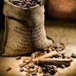 Dark composition of coffee beans and burlap bag — Stock Photo #5070112