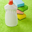 Bottle and sponges on green towel - Foto Stock