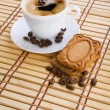Cup of capuchino with coffee beans and cookie on a mat — Stock Photo