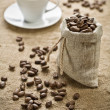 Coffee beans and cup of coffee on sacking — Stock Photo #5078049