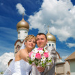 Newlywed couple on background of church — Foto Stock #5079395