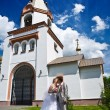 Newly married kiss on a background of church — Stock Photo