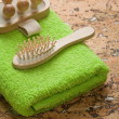 Massager and hairbrush on green towel — 图库照片