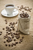 Coffee beans and cup of coffee on sacking — Stock Photo