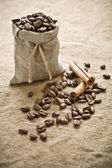 Coffee beans and cinnamon on sacking — Stock Photo
