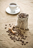 Cinnamon and coffee on sacking — Stock Photo