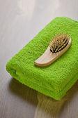 Hairbrush on green towel — Stock Photo