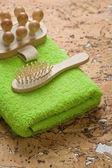 Massageador e escova de cabelo na toalha verde — Foto Stock