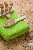 Massager and hairbrush on green towel — Стоковое фото