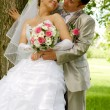 The groom and the bride in park near a tree flirt — Stok fotoğraf