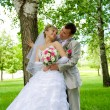 The groom and the bride in park near a tree - Foto Stock