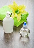 Handdoek met bloem en flessen — Stockfoto