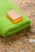 Soap and towel on cork wood — Stock Photo