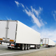 Caravan of white trucks on highway under blue sky — Stock Photo