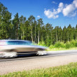 Car speeding on country highway, natural motion blur — Stock Photo