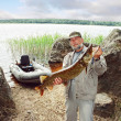 Stock Photo: Angler catch big pike fish, fishing on lake with boat