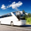 White bus speeding on highway, blurred in motion - Stock Photo