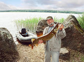 Angler catch big pike fish, fishing on lake with boat — Stock Photo