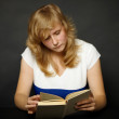 Stock Photo: Womreading book at night