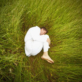 Man lying on grass in fetal position — Stock Photo