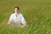 Man sits in grass — Stock Photo