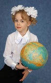 Schoolgirl with geographic globe — Stock Photo