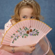 Girl hides behind her fan — Stock Photo
