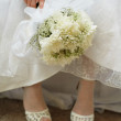 Bouquet of bride against dress and shoes - Stock Photo