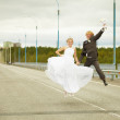 Newly married pair jumps on highway — Stock Photo