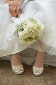 Bouquet of bride against dress and shoes — Stock Photo