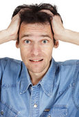 Confused young man has clasped hands a head — Stock Photo