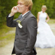 Groom has turned away from bride and speaks on phone - Stock Photo