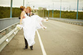 Groom carries his bride in his arms on bridge — Stock Photo