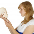 Woman examines a human skull on white — Stock Photo