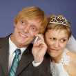 Groom calls on a cell phone, bride overhears - Stock Photo