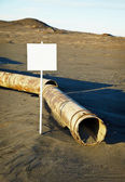 Sign near old rotting pipe - ecological disaster — Stock Photo