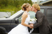 Bride and groom kissing near a car — Stockfoto
