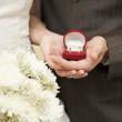 Wedding rings in hands of bride and groom — Stock Photo