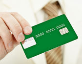 Green electronic plastic card in hand — Stock Photo