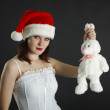 Woman in Christmas cap holds in hand a white rabbit — Stock Photo