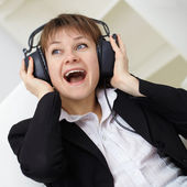 Сheerful woman singing in ear-phones — Stock Photo