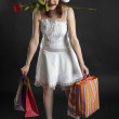 Amusing girl in Christmas cap, with purchases and rose — Stock Photo