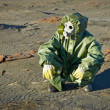 Scientist in protective suit and gas mask sitting on slag — Stock Photo