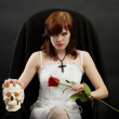 Beautiful girl sitting in chair with skull and rose — Stock Photo