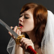 Bride lipstick using reflection in sword — Stock Photo