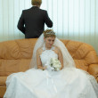 Bride sitting on couch, groom looks out window — Stock Photo