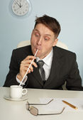 Comic man drinking coffee with long straws — Stock Photo